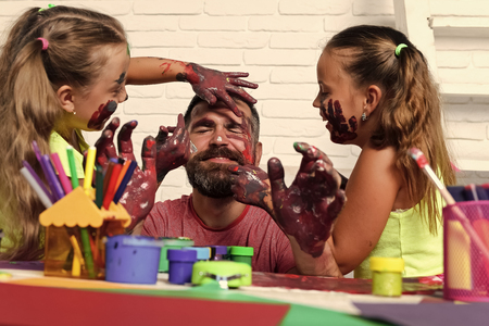 children have fun with their father. Girls drawing on man face skin with colorful paints