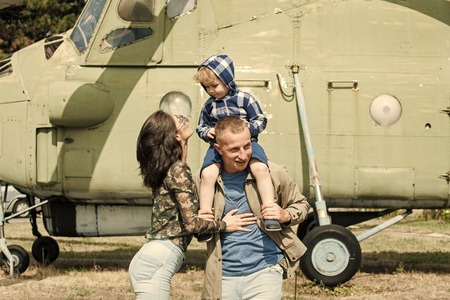 Development and upbringing concept. Mother and father and their child walking in aviation museum outdoors. Happy family spend time together, on excursion, helicopter or plane on background, sunny day