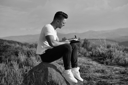 lonely man writes a letter to his beloved. Pensive muscular man with book outdoor