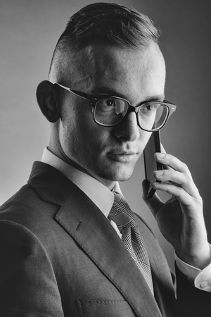 fashion business portrait. Guy in glasses with mobile phone