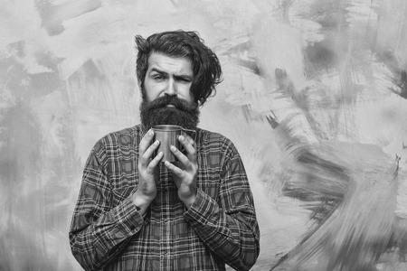 man drinks hot tea. Unhappy bearded man with stylish fringe hair holding metal mug