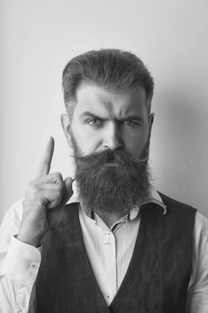 bearded man points. bearded man, brutal caucasian hipster with serious face