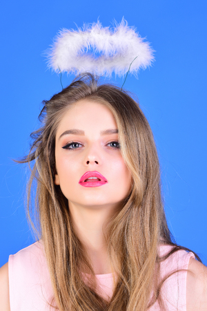 Sexy woman with long hair on blue background. woman with angel halo from feather for valentines day celebration.