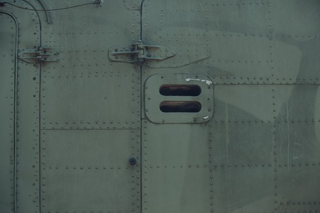 Aircraft covering detail on metallized background. Fuselage metal surface with rivets. Design structure and construction. Aviation and air transport