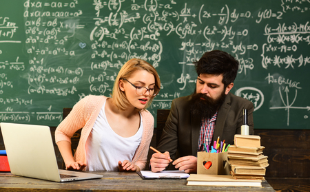 E-learning education and university concept, Tutor asks the tutee to find the definition in the textbook, Home tutor helping boy with studies using modern laptop 写真素材 - 103330068