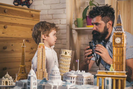 Adventure begin right now. Discovering new places. Little child and man with binocular and miniature architecture. Boy son and father with world landmark buildings in miniature. Looking for adventure 版權商用圖片