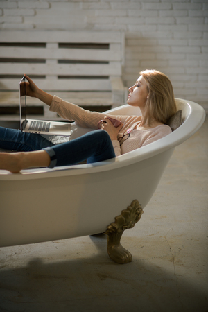 Woman work on computer in home bath. sensual woman in bath with computer.