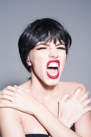 Young woman in strapless top wearing black wig isolated on gray background. Angry female with full red lips screaming from pain, mental suffering concept