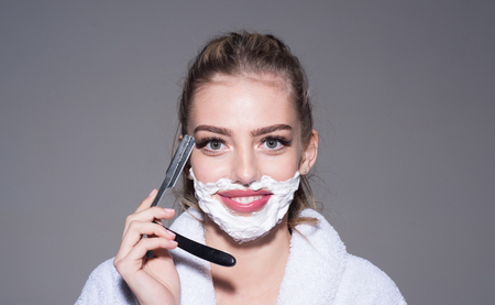 Smiling blond woman with shaving cream on her cheeks holding retro cut-throat razor isolated on gray background. Cheerful girl having fun in bathroom