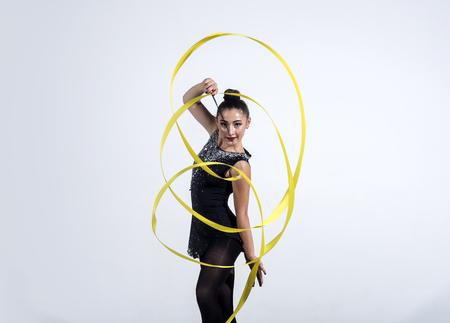 girl train acrobatics with ribbon. girl curl yellow ribbon in rhythmic gymnastics. Imagens