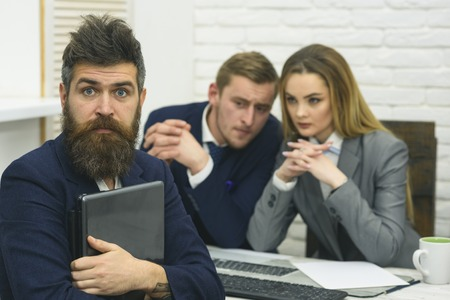 Startup concept. Man with beard and folder proposes extraordinary startup idea. Business negotiations, discuss conditions of deal. Business partners or businessman at meeting, office background