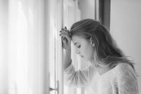 girl is sad at the window. Pretty girl standing at window