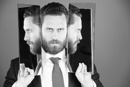 personality disorder. business man with beard, holding mirror with face reflection