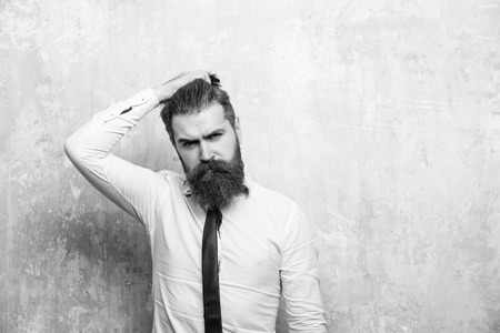 pondered man scratched his head. hipster or bearded man with long beard on serious face Фото со стока