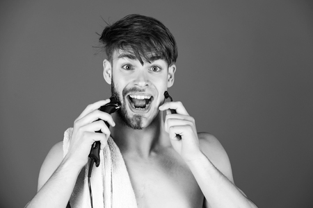 mechanical or electric shaver. guy shaving hair with electric shaver and safety razor