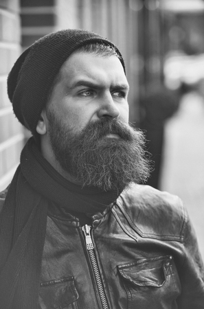 fashion portrait of a brutal man. bearded man hipster with serious face in leather jacket
