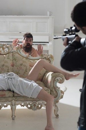 Hipster shocked to see gunman in bedroom. Hipster with hands up look at gun