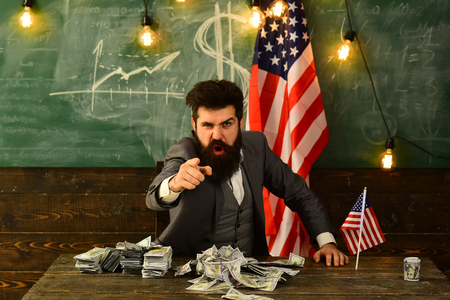 Businessman with money and United States flag representing a strong U.S. economy, strength of the American dollar and power through national wealth Stock Photo