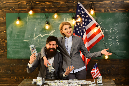 man and woman with money standing over USA flag. happy and embrace. Stock Photo