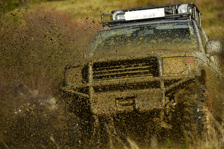 Off road car takes part in racing on nature background. Splash of dirt under SUV on countryside road. Cross country rallying or rally raid Extreme and four wheel drive concept