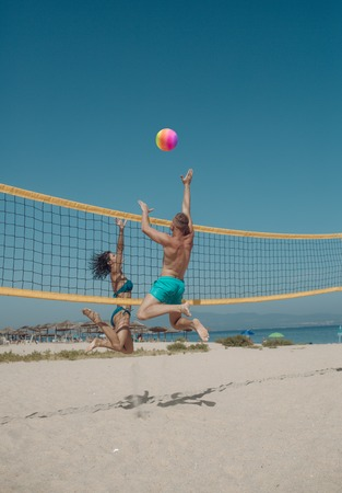 Couple have fun playing volleyball. Young sporty active couple beat off volley ball, play game on summer day. Woman and man fit, strong, healthy, doing sport on beach. Beach volleyball concept