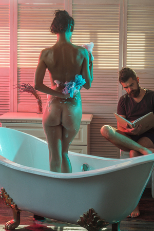 Massage and family spa concept. Bearded man read book while naked girl wash with wisp. Love relations of couple in bath with foam. Couple in love with sexy body. Sex games desire and orgasm