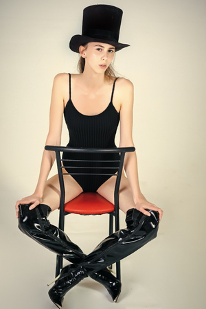 Beauty and fashion. fashion portrait of a sensual sexy girl. Girl in black fashionable swimsuit, hat and boots on chair Stock Photo