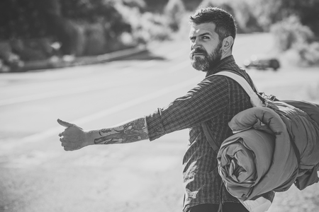 Tourist traveler travel auto stop. Man with backpack hitchhiking on road Stock Photo