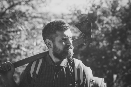 Adventure, discovery, wanderlust. Man lumberjack with beard hold axe on shoulder