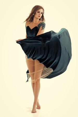 retrato de moda de una chica sensual. Chica posando en vestido de noche azul descalzo