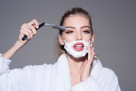Blond woman trimming her eyebrows with cut-throat razor in bathroom, brutal beauty. Beautiful girl with shaving foam on her face isolated on gray background