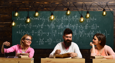 Girls, happy students looking with adoration at bearded teacher, lecturer, professor. College and education concept. Students, young scientists fall in love with professor chalkboard background