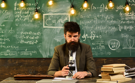 Businessman with glasses and optical instrument at desk. Bearded man work with microscope. Man with beard and mustache in school. Scientist make research on chalkboard. Science and study Stock Photo