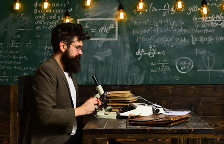 Scientist work with microscope. Man with beard and mustache in school. Bearded man make research on chalkboard. Businessman with glasses and optical instrument at desk. Science and study
