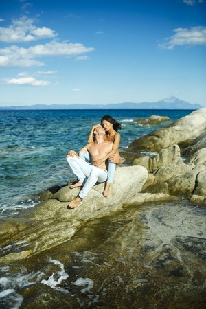 Sensual nude attractive couple on pensive faces. Sexy topless couple sits on stone or reef in sea. Happy family spend time together, hugs and suntanning, sea surface background. Honeymoon concept