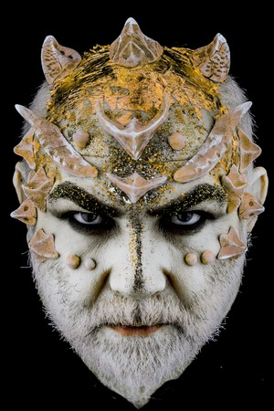 Head with thorns or warts, face covered with glitters, close up. Demon on serious face, black background. Alien, demon, sorcerer makeup. Senior man with beard, with monster makeup. Fantasy concept