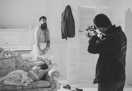 Cheating and jealousy concept. Man at gunpoint of killer. Husband found lovers, killed wife and threatening to bearded lover. Man with beard naked, scared, shocked at gunpoint, interior background