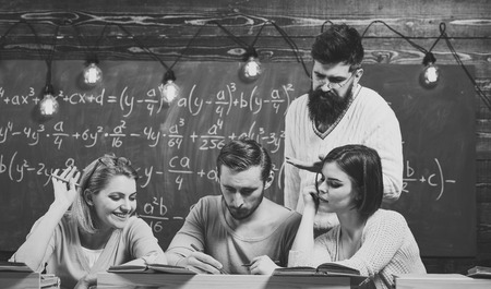 Students, group mates speaking, asking for advice, teacher explains. Studying difficulties concept. Bearded teacher, lecturer, professor teaching students, chalkboard on background. Stock fotó