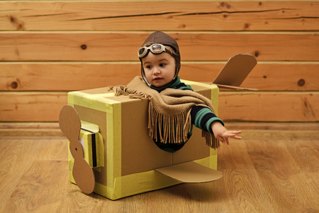 Childhood dream imagination concept . Little cute boy playing with a cardboard airplane.