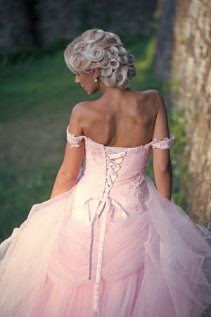 Beauty Fashion model girl. Fashion look. Girl pose in pink dress with open shoulders, back view