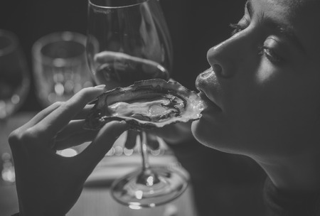 Beauty Fashion model girl. Fashion look. girl or woman eating oyster with wine in luxury restaurant. woman or girl eating oyster in hand and drink red wine Stock Photo