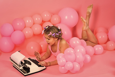 girl is typing on a typewriter. Child in underwear with typewriter on pink background.