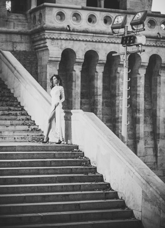 Beauty Fashion model girl. Fashion look. Young woman in white long dress stepping up staircase