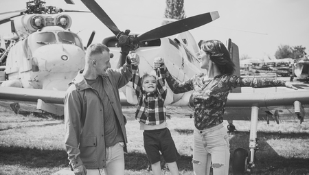 family in the aviation museum. Happy family spend time together, on excursion, helicopter or plane on background, sunny day. Mother and father and their child walking in aviation museum outdoors