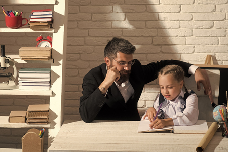 home schooling. Girl and her teacher in classroom on white brick background