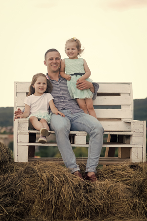 happy father. Man and girls sit on bench on hay