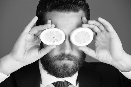 healthy food and dieting. lemon at face of man with beard or businessman