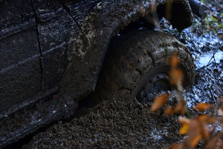 Offroad tire covered with mud overcomes obstacles on nature background. Stock Photo