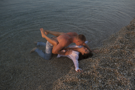 Summer holidays and paradise travel vacation. Love relations of naked couple in sea water. Sexy woman and man have sex games. Family and valentines day. Couple in love with sexy body relax on beach. Stock Photo