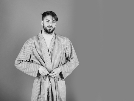 Male fashion, beauty and advertisement concept. Bearded man tying belt in bow on blue robe